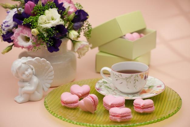 Biscuits roses en forme de coeurs sur une assiette avec des anges et des fleurs le jour de la saint-valentin