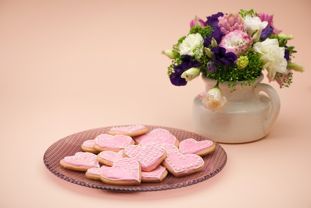 Biscuits roses en forme de coeurs sur une assiette et fleurs le jour de la saint-valentin