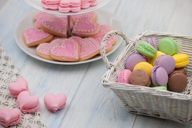 Biscuits roses en forme de coeurs sur une assiette et pâtisseries dans un panier en osier sur les planches de bois