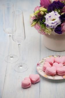 Biscuits roses en forme de coeurs sur une assiette et verres de champagne avec des fleurs