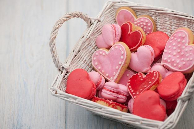 Biscuits roses et rouges en forme de coeur dans un gros plan carré de panier en osier