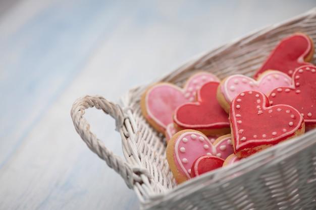 Biscuits roses sous forme de coeurs dans un gros plan carré de panier en osier