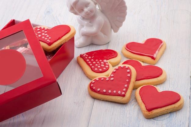 Biscuits rouges en forme de coeur dans une boîte-cadeau et anges sur des planches de bois