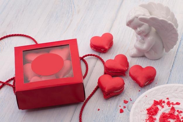 Biscuits rouges en forme de coeur dans une boîte-cadeau sur des planches en bois et un ange le jour de la saint-valentin