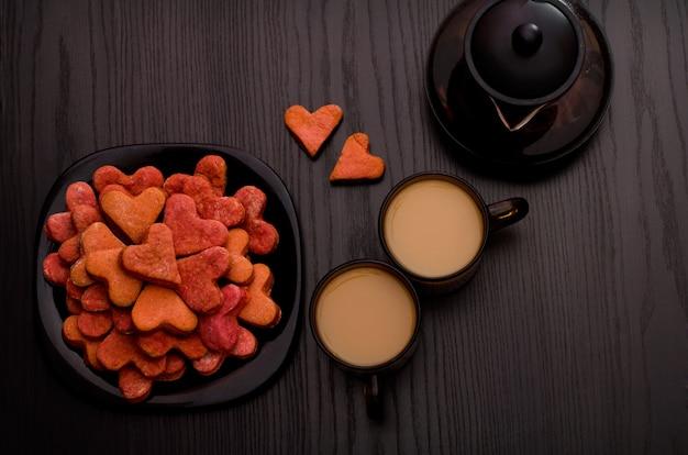Biscuits rouges en forme de coeur, deux tasses de thé avec du lait et une théière. la saint valentin