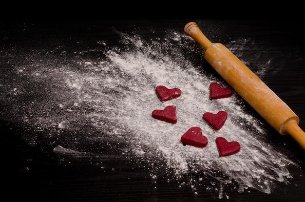 Biscuits rouges en forme de coeur sur une farine, cuisant le jour de la saint-valentin