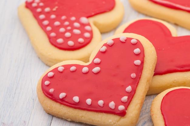 Biscuits rouges en forme de coeur sur des planches de bois en gros plan le jour de la saint-valentin