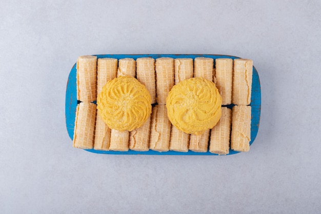 Biscuits sur des rouleaux de gaufres sur le plateau en bois, le marbre.