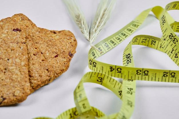 Biscuits et ruban à mesurer sur blanc, gros plan.