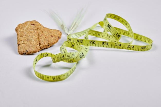 Biscuits et ruban à mesurer sur blanc.