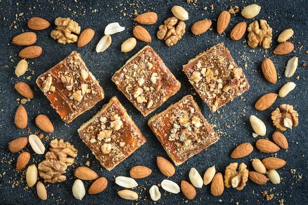 Biscuits sablés au caramel fait maison avec des noix posées sous la forme d'un carré sur fond noir avec des miettes.