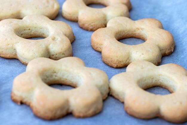 Biscuits sablés cuits au four sous forme de fleurs sur une plaque à pâtisserie avec du papier sulfurisé tout juste sorti du four. snack pour le petit déjeuner. mise au point sélective. vue rapprochée