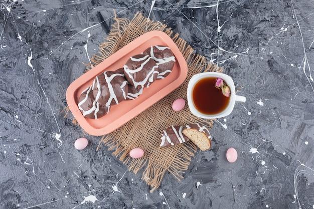 Biscuits sablés enrobés de chocolat blanc et noir avec une tasse de thé en verre.