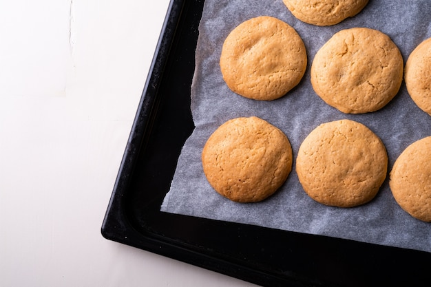 Biscuits sablés faits maison sur papier parchemin dans une plaque à pâtisserie sur table blanche en bois vue de dessus