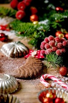 Biscuits sablés de noël traditionnels faits maison croissants de chocolat avec du sucre glace au cacao dans une plaque en céramique avec des moules à biscuits, sapin, décorations d'étoiles de noël rouges sur fond de bois
