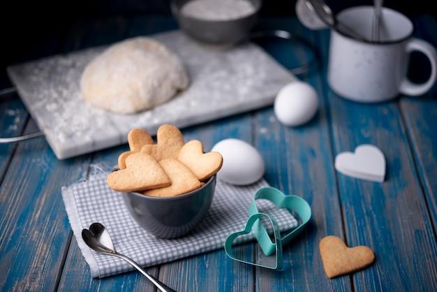 Biscuits de saint valentin dans une tasse avec des œufs et de la pâte