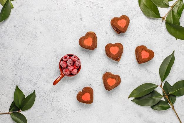 Biscuits de saint valentin en forme de coeur avec des framboises surgelées à la lumière