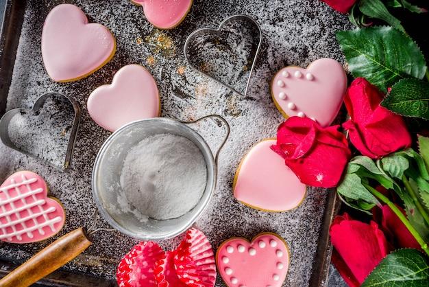 Biscuits de saint valentin sur un plateau plein de sol et de roses