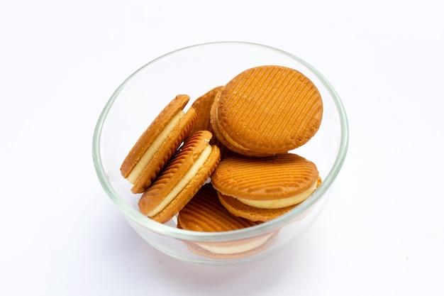 Biscuits sandwich à la crème pâtissière dans un bol en verre sur fond blanc.
