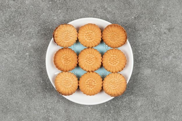 Biscuits sandwich remplis de crème sur plaque blanche