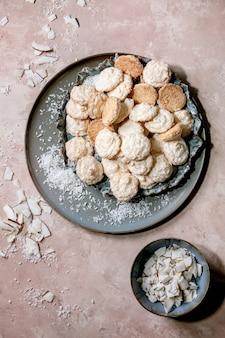 Biscuits sans gluten de noix de coco faits maison avec des flocons de noix de coco sur une plaque en céramique sur une surface de texture rose. mise à plat, espace de copie