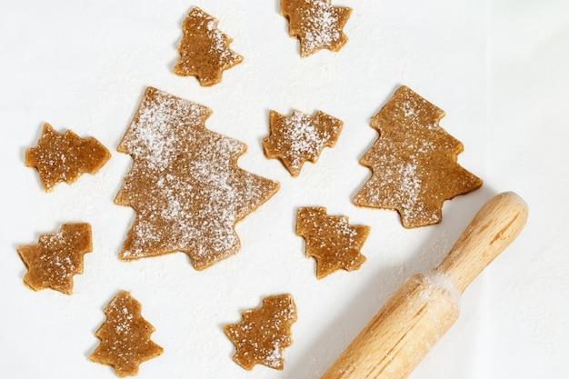 Biscuits de sapin de noël sur papier pour la cuisson.