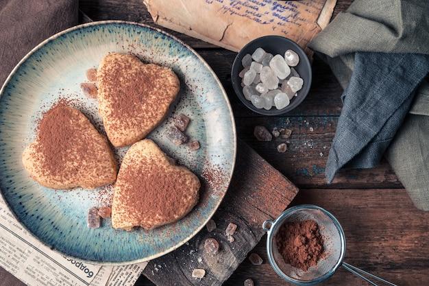Biscuits saupoudrés de cacao sur un fond en bois. la vue du haut.