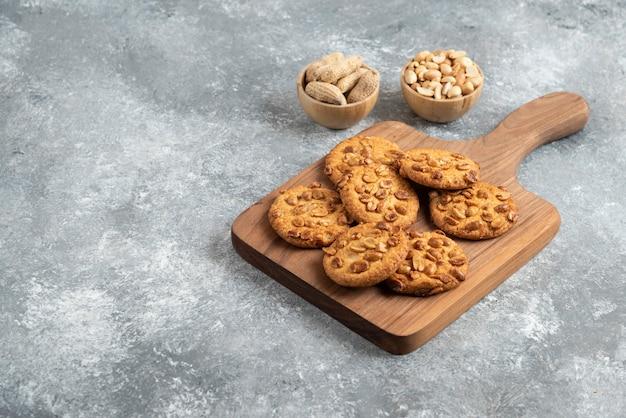 Biscuits savoureux avec des arachides biologiques et du miel sur planche de bois.