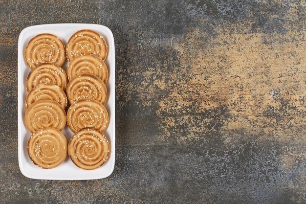 Biscuits savoureux aux graines de sésame sur plaque blanche.