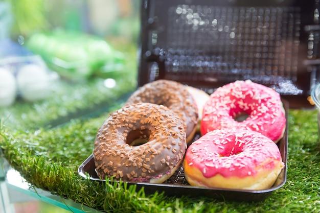 Biscuits savoureux dans un récipient en plastique sur l'herbe