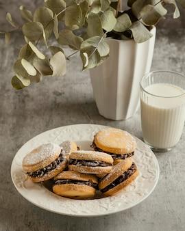 Biscuits savoureux fourrés au chocolat sur plaque