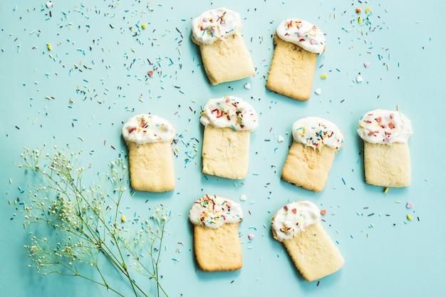 Biscuits sous forme de gâteaux de pâques sur fond bleu parmi les fleurs de gypsophila