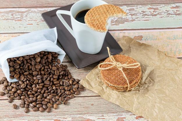 Biscuits stroopwafel avec un arc en sisal à côté des haricots et une tasse de café.
