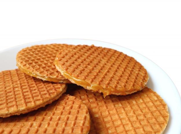 Biscuits stroopwafel, bonbons traditionnels néerlandais servis sur une plaque blanche isolée sur fond blanc