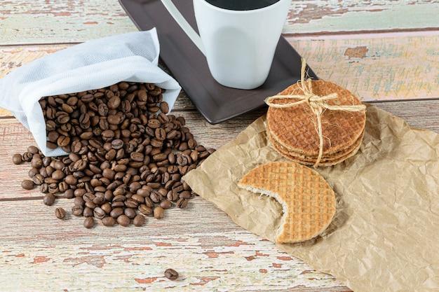 Biscuits stroopwafel avec une bouchée à côté des haricots et une tasse de café.