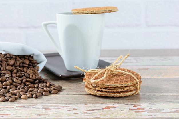 Biscuits stroopwafel avec un nœud en sisal à côté d'une tasse de café (vue latérale).