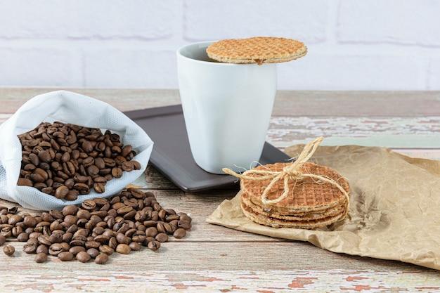 Biscuits stroopwafel avec un nœud en sisal à côté d'une tasse de café.