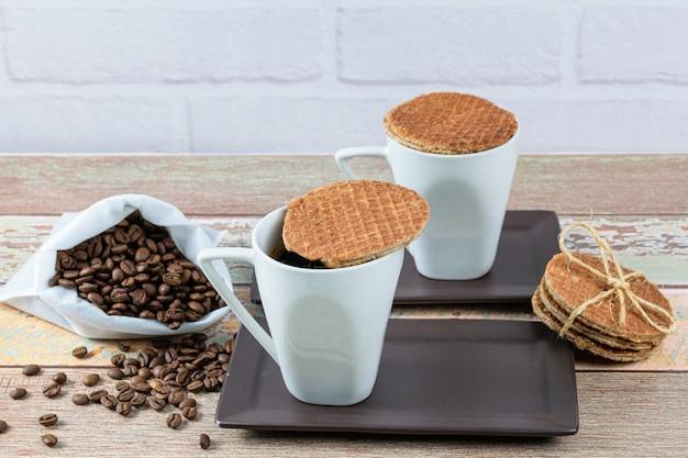 Biscuits stroopwafel servis avec des tasses de café.