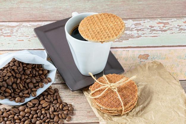 Biscuits stroopwafel sur une tasse de café à côté de grains torréfiés.