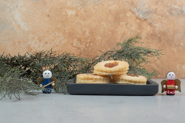 Biscuits sucrés avec de la confiture sur un tableau noir et des jouets
