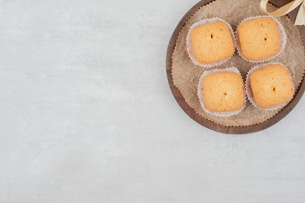 Biscuits sucrés à la crème sur une assiette en bois décorée de ruban.