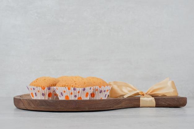 Biscuits sucrés à la crème sur une plaque en bois décorée de ruban.