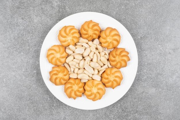 Biscuits sucrés faits maison et noix de cajou sur plaque blanche