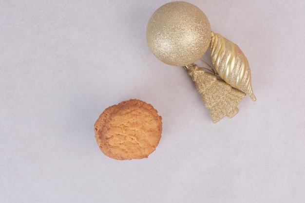 Biscuits sucrés avec des jouets de noël dorés sur une surface blanche
