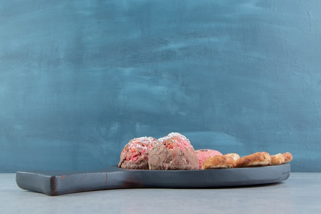 Biscuits sucrés avec des paillettes sur une planche de bois sombre.