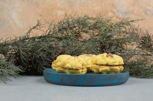 Biscuits sucrés ronds avec confiture sur plaque