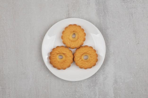 Biscuits sucrés savoureux sur plaque blanche.