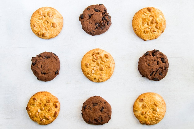 Biscuits sur table blanche, dessert pâtissier au chocolat et noix, vue du dessus