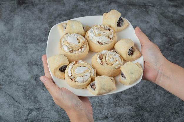 Biscuits traditionnels du caucase avec du sucre en poudre sur le dessus sur une plaque en céramique blanche.