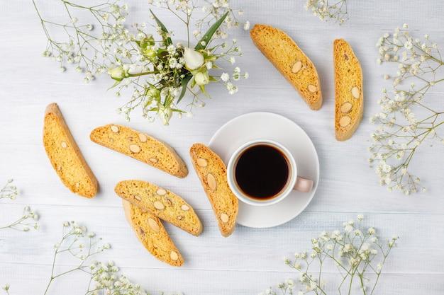 Biscuits traditionnels toscans italiens cantuccini aux amandes, une tasse de café à la lumière